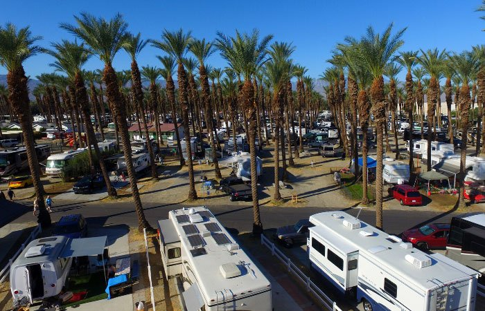 Aerial view of RVs in a campground filled with palm trees