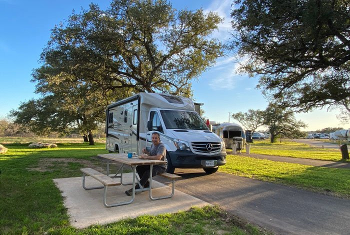 woman at picnic table with RV Rental in background