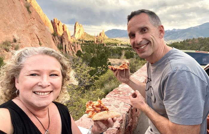 couple eating pizza with Garden of the Gods backdrop