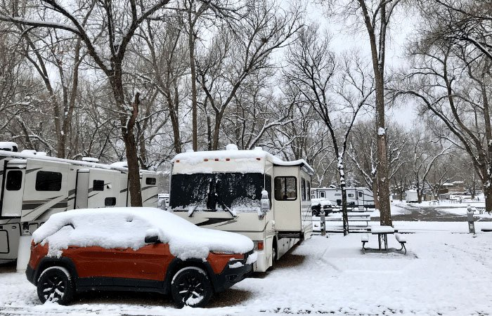 Snow covered RV and Jeep in campground