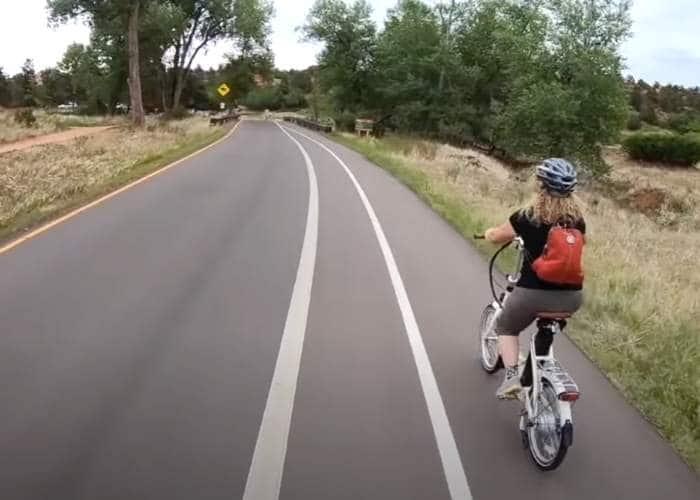 woman riding bike in bike lane in park area