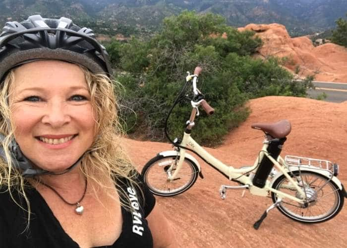 close up of woman smiling with bike in background