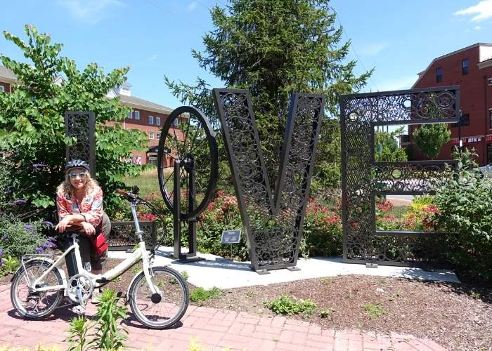woman and bike in front of large LOVE sign