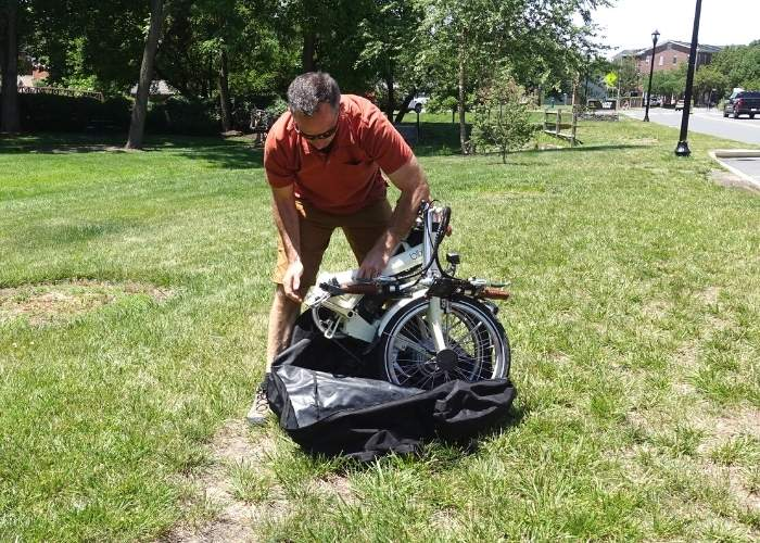 man pulling folded up bike out of a bag in grassy area