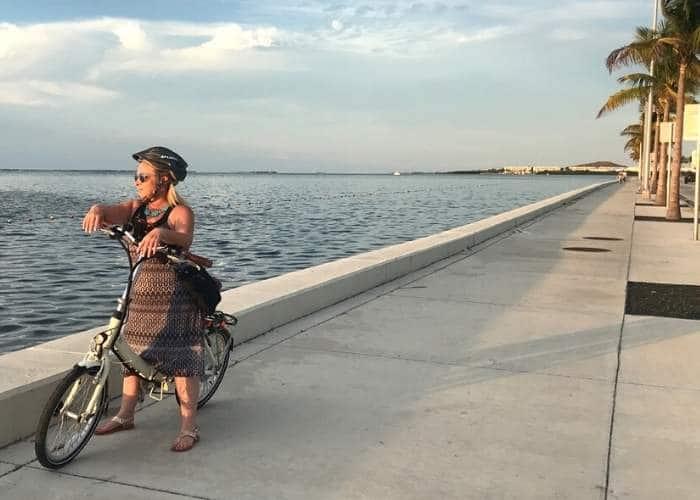 woman on blix bike on sidewalk near ocean in key west Florida