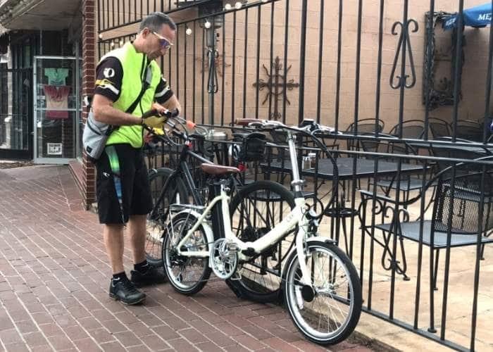 man locking bike to metal fence on brick sidewalk