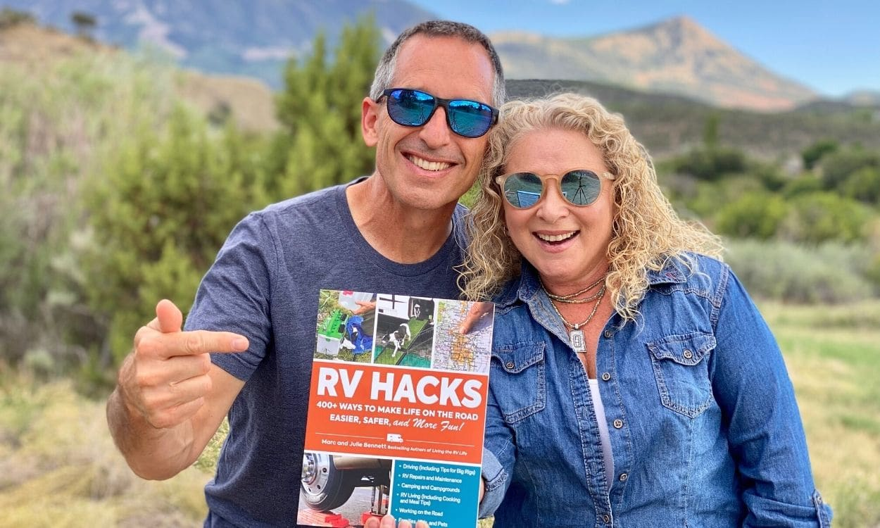 MARC And julie bennett of rvlove holding RV HACKS book with mountain backdrop