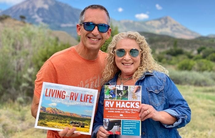 marc and julie of RVlove hold their 2 books with mountain backdrop